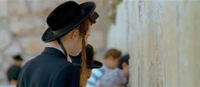 A Hassidic (ultra-orthodox) Jewish boy/man with peyot/peyas (religiously uncut portions of the hair before the ears) and Tefilim (religious boxes with Hebrew scrolls within strapped to the forehead and arm) davening (praying) before the Kotel (Western Wall, Wailing Wall, etc) in Jerusalem, Israel.