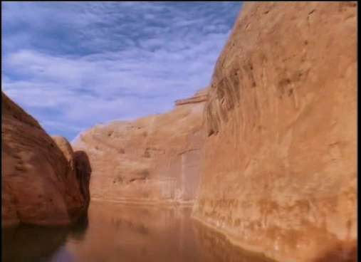 Location: Glen Canyon National Recreation Area (Lake Powell).   There are countless narrow canyons having still water such as this. Depending on the specific location - as Lake powell is said to have approximately 2,000 miles of shoreline - this formation is either the Cedar Mesa formation of Permian age, or the Navajo Sandstone of Jurassic age. The northern end of Lake powell has a greater exposure of the former, whilst the mid-to-southern end has greater amounts of Navajo Sandstone.