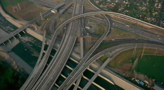 Freeway interchange, possibly in Los Angeles judging by the concrete flood-divert (LA River?) at the left and bottom.