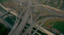 Freeway interchange, possibly in Los Angeles judging by the concrete flood-divert (LA River?) at the